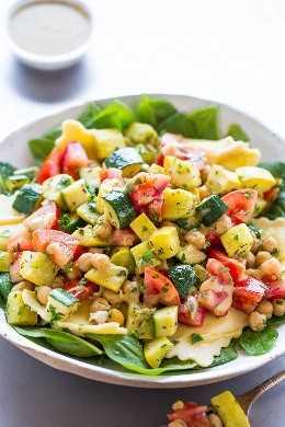 Ensalada de raviolis y espinacas de verduras de verano: calabacín crujiente y tierno, calabaza amarilla, tomates y garbanzos sobre espinacas con ravioles cursi y una vinagreta de dijon. ¡Una ensalada saludable pero abundante que aprovecha el VERANO!