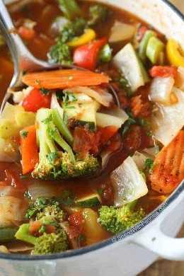 Sopa de verduras en un tazón con cucharón plateado
