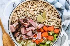 Ingredientes jamón y frijoles en una olla de caldo.