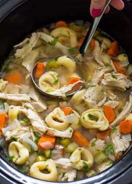 Sopa de tortellini de pollo a fuego lento en una olla de cocción lenta con cucharón