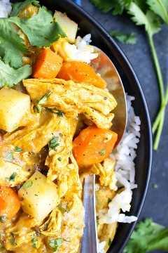 Un primer plano de una cuchara conseguir un bocado de pollo al curry amarillo con patatas y zanahorias.