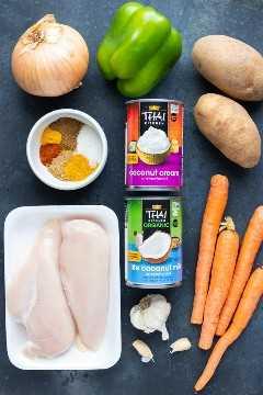 Pechugas de pollo, mezcla de condimentos al curry, leche y crema de coco, zanahorias, papas y cebolla como ingredientes en una receta de pollo al curry amarillo.