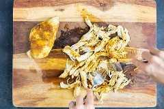 Pollo al curry desmenuzado con dos tenedores en una tabla para cortar madera.