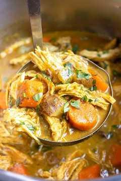 Un cucharón sacando una porción de pollo al curry amarillo de una olla instantánea de 6 cuartos.