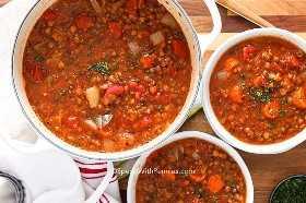 Una olla de sopa de lentejas se sirve en 2 platos hondos.