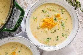 Una porción de sopa de queso de brócoli con queso rallado.