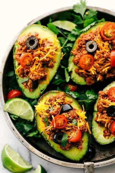 Aguacate relleno de taco de pavo en una sartén con rodajas de limón.