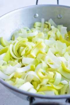 Un colador lleno de puerros en rodajas finas y limpias para una receta de sopa de puerros y papas.