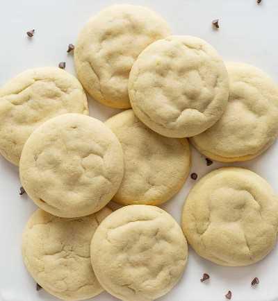 Vista aérea de galletas de azúcar con relleno de pastel de queso con chispas de chocolate en bandeja blanca