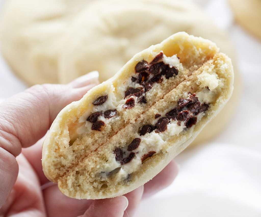 Galletas de azúcar con relleno de pastel de queso con chispas de chocolate rotas por la mitad