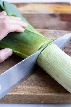 Una imagen que muestra cómo cortar puerros frescos para usar la parte blanca de la sopa y descartar la parte verde.
