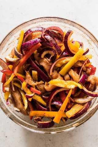 Pimientos, cebollas y pechuga de pollo en rodajas sazonada con condimentos de fajita.