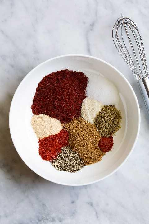 Condimento para tacos en un tazón que muestre todas las especias por separado antes de mezclar.