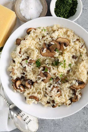 Un plato de risotto de champiñones adornado con parmesano y perejil.
