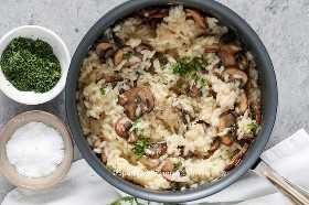 Un plato de risotto de champiñones adornado con perejil y parmesano.