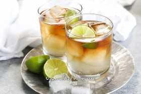 Dos cócteles oscuros y tormentosos preparados en una bandeja con rodajas de limón.