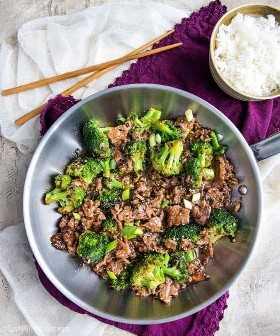 Carne de res y brócoli en una sartén de acero inoxidable con un tazón de arroz con palillos en el fondo