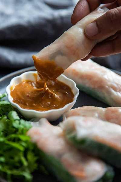 Rollitos de gambas se sumergen en una salsa.