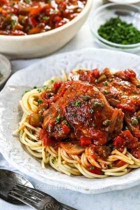 Una porción de pollo cacciatore sobre fideos de espagueti.