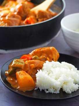 caldereta de pollo con arroz al vapor en un plato negro