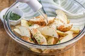 Cuñas de papa cubiertas con aceite de oliva, condimentos y queso parmesano.