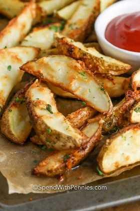 Ciérrese para arriba de las cuñas de patata cocidas crujientes en una bandeja de la hornada con un plato de salsa de tomate.