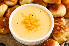 Beer cheese sauce in a bowl topped with cheddar cheese and surrounded by soft pretzel bites