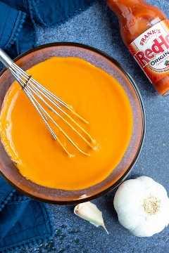 Una receta fácil de salsa de alitas de búfalo hecha con salsa candente de Frank, ajo y mantequilla.