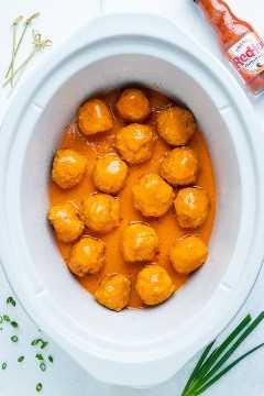 Una olla de cocción lenta de 6 cuartos llena de albóndigas fáciles y bajas en carbohidratos cubiertas con una salsa de búfalo.