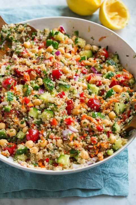 Ensalada de quinua saludable en un tazón para servir. La ensalada muestra quinua, pepino, tomate, zanahoria, cebolla roja, garbanzos y hierbas.
