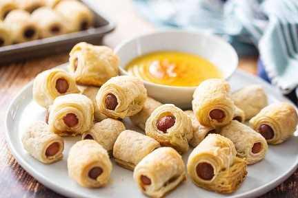 Cerdos en una manta, desde cero, dispuestos en una fuente con un tazón pequeño de salsa de miel y mostaza.