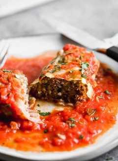 Rollos de col rellena en un plato cortado por la mitad con salsa y cubriendo el plato.