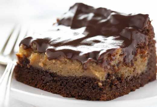 Pedazo de mantequilla de maní de chocolate Ooey Gooey Cake en un plato blanco con tenedor