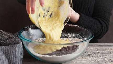 Verter los ingredientes húmedos en seco para pan de plátano con chispas de chocolate.
