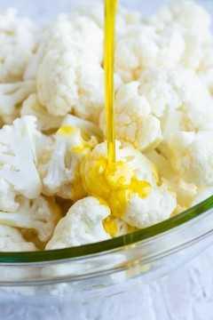 El aceite de oliva se vierte en las flores de coliflor antes de asar en el horno.