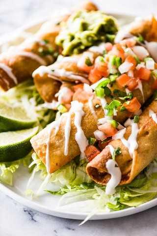 Taquitos crujientes rellenos de pollo y cubiertos con ingredientes mexicanos