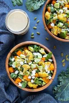 Dos cuencos de madera llenos de una saludable ensalada casera de verduras asadas con coliflor y calabaza.
