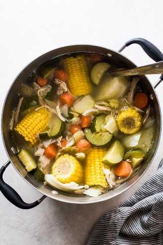 Caldo de pollo en una olla con un cucharón.