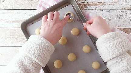 Presionando la parte posterior de una cuchara dosificadora en la masa de galletas con huella digital para hacer un pozo para la mermelada.