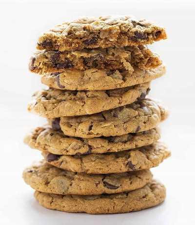 Pila de galletas de chispas de chocolate de mantequilla de maní sin harina con galleta rota en la parte superior