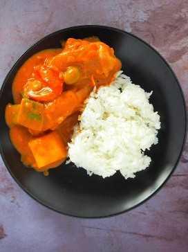 Vista superior de caldereta de pollo con arroz al vapor en un plato de servir negro