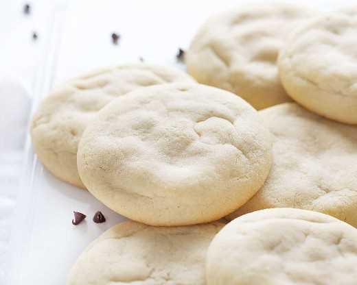 Galletas de azúcar con relleno de pastel de queso con chispas de chocolate apiladas en un plato blanco