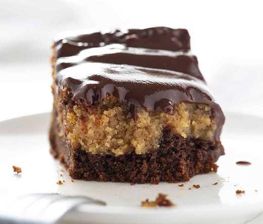 Pastel de chocolate con mantequilla de maní Ooey Gooey con tenedor descansando sobre un plato blanco