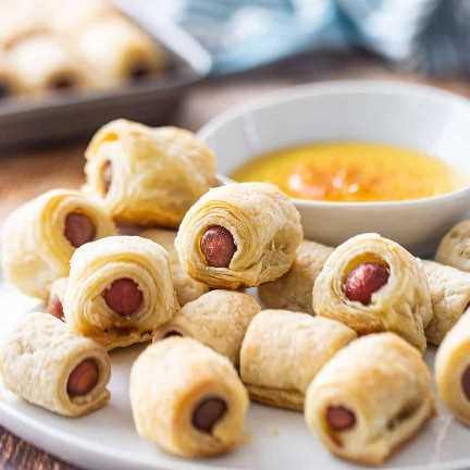 Cerdos en una manta en un plato con salsa de mostaza y miel.