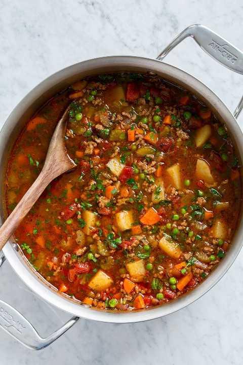 Olla llena de sopa de hamburguesas con carne molida, papas, guisantes, zanahorias, apio, tomates y condimentos.