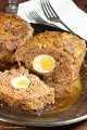 Un pastel de carne con huevos duros en el medio.