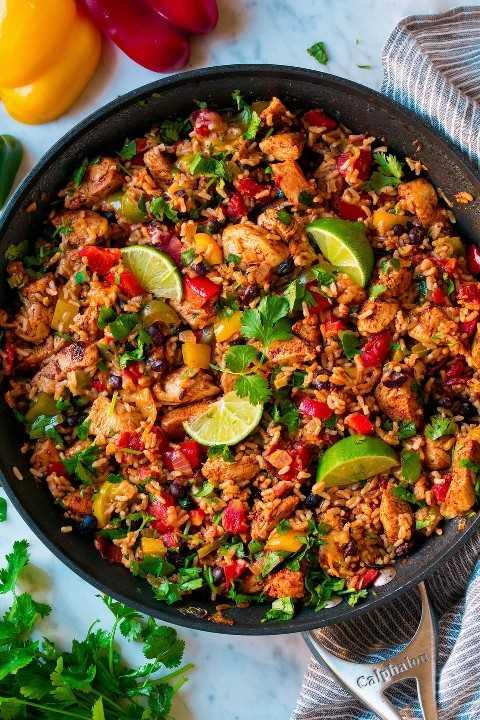Se muestra un tazón de arroz con fajita de pollo después de cocinar en una sartén. Incluye arroz integral, pollo, frijoles negros y pimientos.