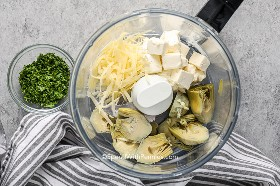 Ingredients for a creamy artichoke sauce in a food processor