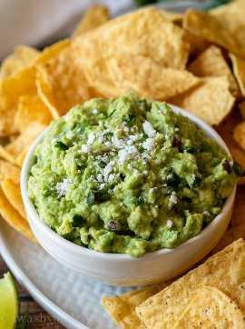 ¡Cubre tu auténtica receta de guacamole con queso cotija fresco y sírvelas con chips de tortilla!