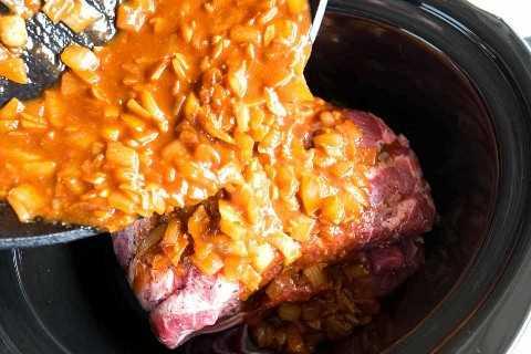 Una mezcla de cebollas y especias que se vierte sobre una paleta de cerdo deshuesada cruda colocada dentro de una olla de cocción lenta.